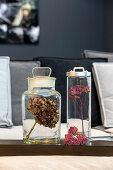 Dried hydrangea and yarrow flower heads in glass jars