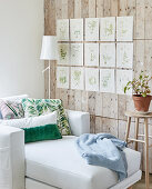 Couch below botanical illustrations on board wall