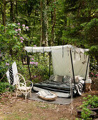 Canopy bed with black-and-white accessories in woodland clearing