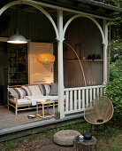 Rattan couch and arc lamp on wooden veranda