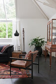 Sofa, wooden trunk and leather chair in front of window in high-ceilinged living room