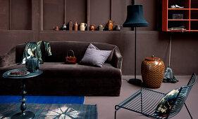 Brown sofa below ornaments on ledge in brown wall