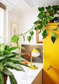 Gelber Schrank mit Zimmerpflanze neben Tisch mit Lampe