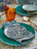 Table set with various floral patterns in shades of blue and green