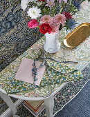 Top of console table covered with floral wallpaper