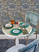 Set table with floral top next to wall with vintage-style floral wallpaper