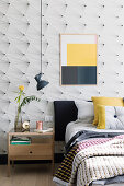 Picture with blocks of colour on wallpaper with graphic pattern in bedroom