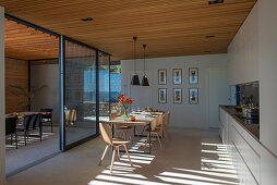 Open-plan interior of modern, architect-designed house with glass walls