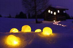 Windlichter aus Eis im Schnee vor beleuchtetem Weg zur Hütte