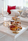 Pastries on golden cake stand on coffee table in living room