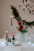 Table festively set for Christmas with red candles and amaryllis