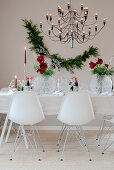 Designer chairs around table set for Christmas decorated with amaryllis