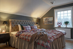 Tartan bed linen on bed with valance in cosy bedroom