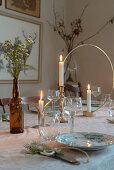 Table set in Bohemian style with candles in golden candlesticks