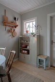 Old cabinet against grey wall in simple kitchen-dining room