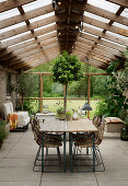 Two beer-garden tables used as dining table in simple conservatory