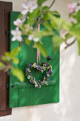 Heart-shaped wreath of lily-of-the-valley and forget-me-nots on window shutter
