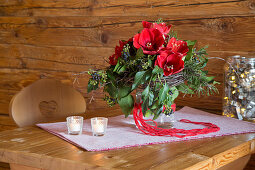 Bouquet with red amaryllis, ivy and ivy berries on wooden table