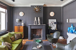 Various seating and fireplace in living room with dark grey walls