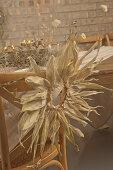 Kranz aus Maisblättern am Stuhl an rustikal gedecktem Tisch