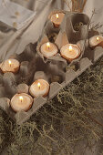 Eierschalen mit Kerzen in Eierkartons als Deko