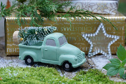 Christmas arrangement with miniature Christmas tree on back of mint-green toy truck