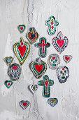 Selbstgemachte Votivgaben aus Prägefolie in Herz-, Kreuz- oder Totenkopfform