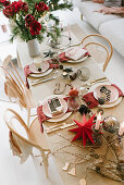 Table set for Christmas meal with red paper star and vase of amaryllis