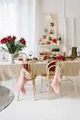 Table set for Christmas meal with vase of amaryllis and stockings hung from chair backs