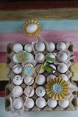 Papierrosetten und kleine Fahnen auf einer Eierpalette mit weißen Eiern