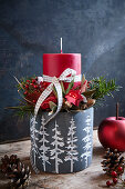 Festive arrangement with red candle in grey flower pot