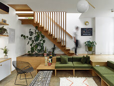 Built-in sofas with green cushions below wooden platform with staircase leading to upper storey