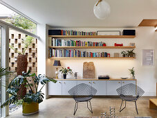 Floating sideboard and shelves next to glass wall overlooking courtyard garden