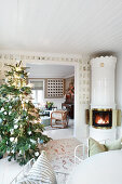 Decorated Christmas tree and Swedish tiled stove in rustic living room