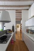 Moderne Küche mit Gasherd im rustikalen offenen Wohnraum