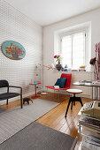 Arbeitszimmer mit grafischer Tapete und verschiedenen Stühlen