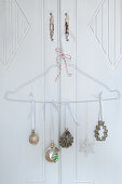 Christmas ornaments and cookie cutters hung on wire hangers as door decorations