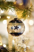 Silver-and-blue Christmas bauble hung from branch in front of sparkling lights