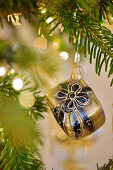 Gift-shaped Christmas bauble hanging from branch