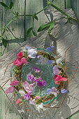 Wreath of willow branches and sweet peas on a glass bowl