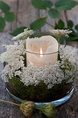 Wreath of Queen Anne's lace flowers arranged around candle lantern