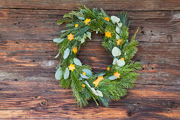 Festive wreath made from various branches and decorations cut out of orange peel