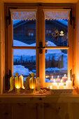Engel aus Goldfolie und Kerzendeko am ländlichen Fenster
