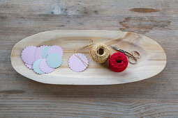 Punched paper, scissors and reels of thread in wooden dish