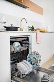 An open built-in dishwasher in a white kitchen