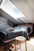 A double bed and motif wallpaper in an attic bedroom