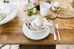A white Easter place setting with a cloth napkin