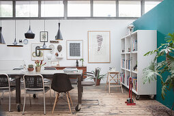 A dining table with classic chairs and open shelving in a loft apartment