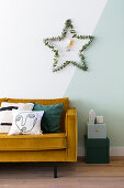 Star of eucalyptus twigs on two-tone wall above sofa