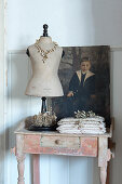 A dressmaker's dummy and a painting on an old wooden table